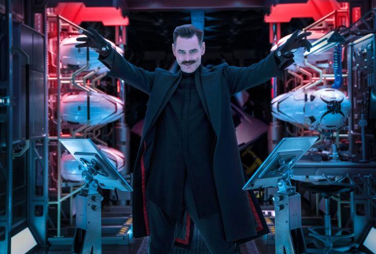 Jim Carrey dressed in all-black wardrobe standing in a room full of robotics.