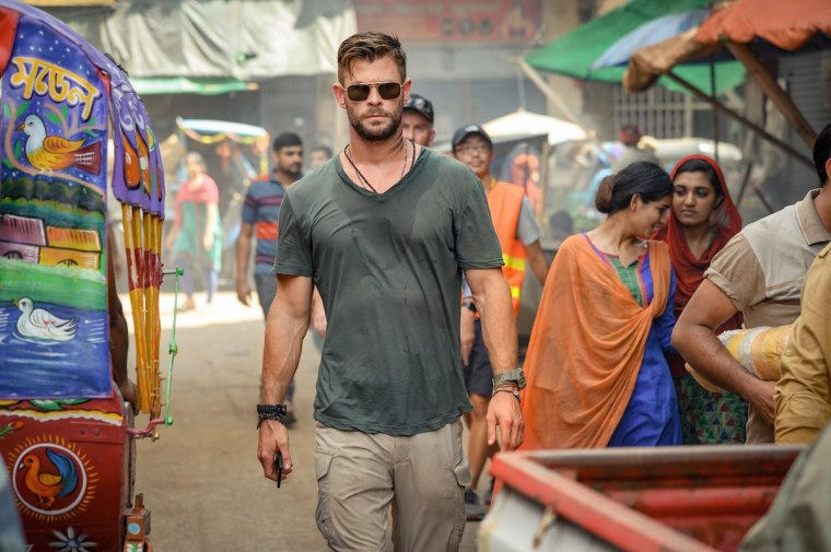 man in sweat-stained grey shirt walks among a crowd in India