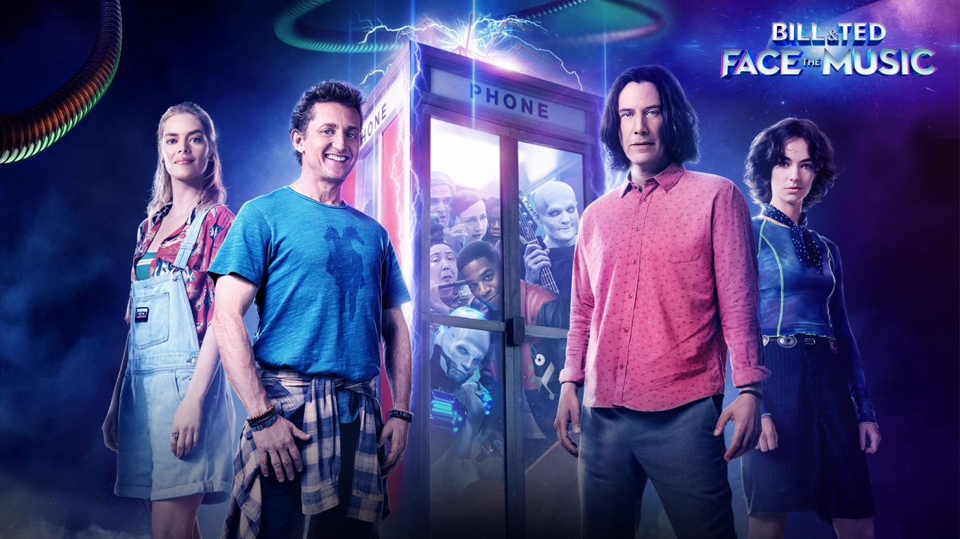 two men and two teenage girls stand next to a magical looking phone booth