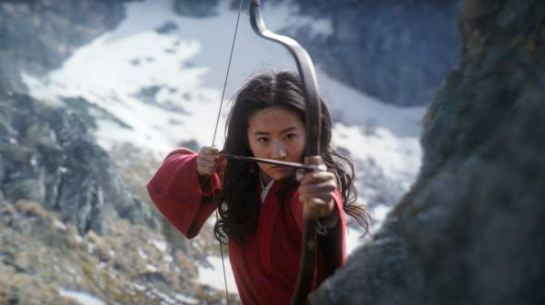 woman in a red robe aims a bow and arrow