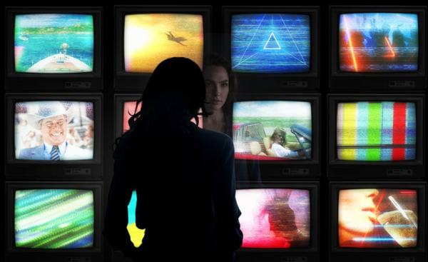 woman looks at multiple television screens