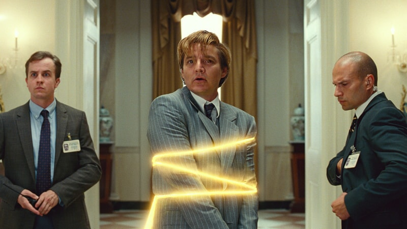 men in suits in a white room with one of them wrapped in a glowing yellow rope