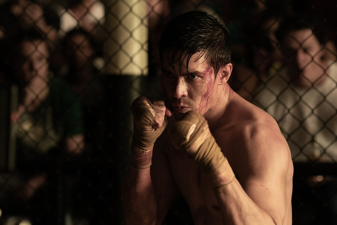 shirtless man fighting in cage