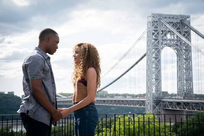 man and woman hold hands in front of New York City bridge